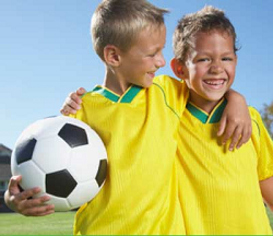Two boys in uniform with a soccer ball
