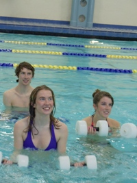 Two women and one man in a pool participate in water based fitness