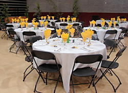 Tables and chairs set up with place settings and decorations